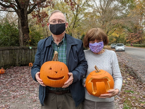 couple holding carved pumpkins